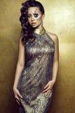 O retrato do modelo de cabelo escuro lindo com o pulso de disparo criativo artístico compõe o vestido de noite dourado luxuoso ve fotografia de stock