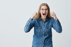 O retrato do modelo fêmea extático entusiasmado com cabelo louro, espetáculos, na camisa da sarja de Nimes, aperta os punhos com  Imagem de Stock Royalty Free