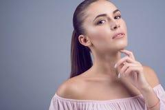 O retrato do modelo novo de cabelo escuro bonito com pele perfeita e o nude molhado compõem no fundo cinzento Foto de Stock