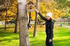 O retrato do outono da mulher bonita sobre o amarelo sae ao andar no parque na queda Emoções e conceito positivos da felicidade imagens de stock