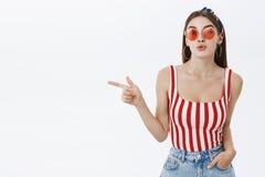 O retrato do party girl em óculos de sol à moda e nos bordos superiores da dobradura do pino-acima listrado divertiu apontar a es imagem de stock royalty free