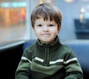 O retrato do rapaz pequeno em uma camisola feita malha, senta-se em um s imagem de stock royalty free