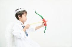 O retrato do rapaz pequeno finge como o cupido com asa e seta Fotografia de Stock
