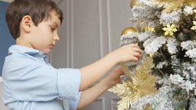 O retrato do rapaz pequeno toca em um brinquedo em uma árvore de Natal filme