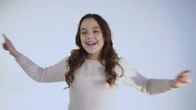 O retrato do sorriso e da menina alegre dança na câmera no fundo branco vídeos de arquivo