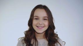 O retrato do sorriso e da menina alegre olha a câmera no fundo branco video estoque