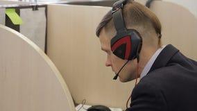 O retrato do trabalhador do apoio da TI que senta-se na tabela e que fala ao cliente em fones de ouvido vídeos de arquivo