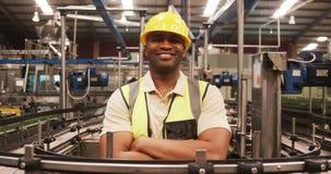 O retrato do trabalhador que está com braços cruzou-se perto da linha de produção vídeos de arquivo