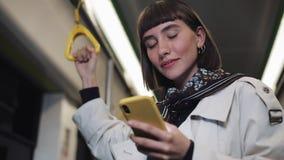 O retrato do transporte bonito de sorriso da jovem mulher em público guarda o corrimão e a consultação no smartphone amarelo cida filme