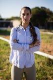 O retrato do veterinário fêmea com braços cruzou a posição no celeiro foto de stock royalty free