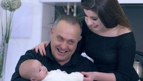 O retrato do vovô com neto e filha em casa, avô feliz guarda o bebê nas mãos filme