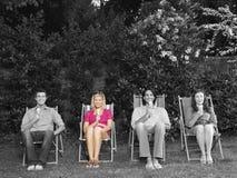 O retrato dos amigos novos felizes que sentam-se na cadeira de plataforma com gelado no quintal Foto de Stock