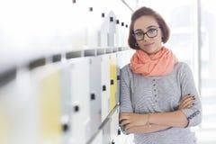 O retrato dos braços eretos da mulher de negócios segura cruzou-se no vestuário no escritório criativo fotos de stock royalty free