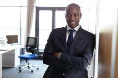 O retrato dos braços eretos de sorriso do homem de negócios novo cruzou a inclinação no armário no escritório Fotos de Stock