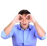O retrato dos jovens surpreendeu o homem que olha através de seus dedos como imagem de stock