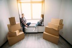 O retrato dos pares novos que movem-se na casa nova que senta-se na soleira e toma uma ruptura imagem de stock