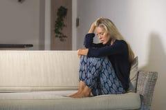 O retrato dramático do estilo de vida da mulher atrativa e triste que sente frustrada e ansiosa sentando em casa o sofá do sofá c imagens de stock