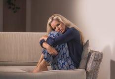 O retrato dramático do estilo de vida da mulher atrativa e triste que sente frustrada e ansiosa sentando em casa o sofá do sofá c foto de stock