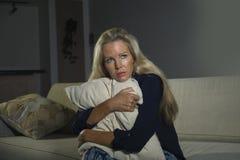 O retrato dramático do estilo de vida da mulher atrativa e triste que sente frustrada e ansiosa sentando em casa o sofá comprimiu imagens de stock