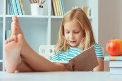 O retrato engraçado de pouca menina da escola que relaxa lê o livro na tabela na sala em casa imagem de stock royalty free