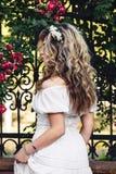 O retrato exterior da menina encaracolado bonita nova próximo forjou a estrutura com rosas fotos de stock