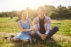 O retrato exterior da menina feliz com cabelo sacudido vestiu-se no vestido azul que senta-se perto de seu amigo que tem o divert imagem de stock royalty free