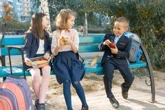O retrato exterior de estudantes da escola primária com lancheiras, crianças saudáveis do café da manhã da escola come, fala, ri imagem de stock