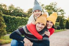O retrato exterior do homem considerável dá o reboque a sua esposa e a filha, veste a roupa morna, tem expressões felizes, apoia  fotografia de stock