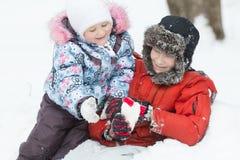 O retrato exterior gelado de dois irmãos de jogo no monte de neve do inverno com coração da neve deu forma à figura Fotografia de Stock