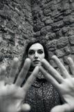O retrato exterior preto e branco da mulher bonita cobre a câmera por suas mãos Fotos de Stock