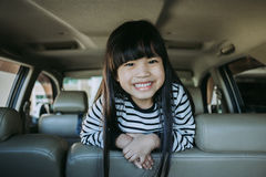 O retrato feliz, criança de sorriso que senta-se no carro que olha para fora janelas, apronta-se para a viagem das férias Imagem de Stock Royalty Free