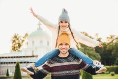 O retrato horizontal do pai afetuoso dá o passeio do reboque a sua filha fora, jogo junto, tem o divertimento Ch pequeno feliz fotos de stock royalty free