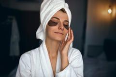 O retrato interno da mulher bonita após o banho com a toalha na cabeça põe remendos sob os olhos dos enrugamentos e dos círculos  fotos de stock