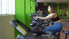 O retrato lateral horizontal da mulher em calças azuis e na parte superior preta que trabalham na bicicleta de exercício na aptid vídeos de arquivo