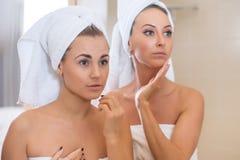 O retrato limpo da pele de Skincare das mulheres com a toalha na cabeça que toca em suas caras refletiu no espelho Imagem de Stock Royalty Free