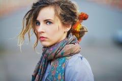 O retrato lindo de uma menina séria nova com olhos azuis bonitos e o cabelo jovem no lenço colorem a imagem Foto de Stock