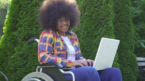 O retrato a mulher afro-americano de sorriso que com um penteado afro desabilitou em uma cadeira de rodas usa um portátil que olh vídeos de arquivo