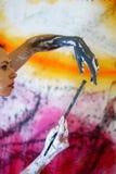O retrato perfila de uma jovem mulher que guarda uma escova e pinta suas mãos na frente do fundo artístico colorido imagens de stock