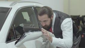 O retrato que o homem farpado seguro atrativo em um terno de negócio inspeciona comprou recentemente auto do concessionário autom video estoque