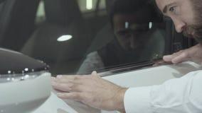 O retrato que o homem farpado seguro atrativo em um terno de negócio inspeciona comprou recentemente auto do concessionário autom vídeos de arquivo
