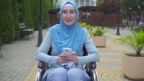 O retrato que a mulher muçulmana atrativa nova desabilitou em um lenço tradicional em uma cadeira de rodas usa um smartphone que  vídeos de arquivo