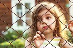 O retrato tonificado da menina bonito triste olha através da cerca de fio Imagens de Stock
