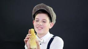 O retrato, um menino bonito em um tampão e os suspensórios jogam com um patinho amarelo pequeno Vídeo do estúdio com decoração te vídeos de arquivo