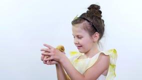 O retrato, uma menina consideravelmente bonito joga com um patinho amarelo pequeno Vídeo do estúdio no fundo branco vídeos de arquivo