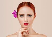 O retrato vermelho bonito da mulher do cabelo com a flor no cabelo perfeito compõe o tratamento de mãos fotografia de stock