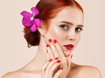 O retrato vermelho bonito da mulher do cabelo com a flor no cabelo perfeito compõe o tratamento de mãos imagem de stock