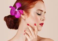 O retrato vermelho bonito da mulher do cabelo com a flor no cabelo perfeito compõe o tratamento de mãos imagens de stock