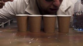 O revestimento branco vestindo do laboratório do homem farpado tenta lamber a água de quatro copos de papel vídeos de arquivo