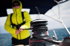 O revestimento do marinheiro puxa o guincho da corda no iate da navigação fotos de stock royalty free