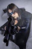 O revólver, mulher perigosa vestiu-se no látex preto, armado com a arma. Foto de Stock Royalty Free